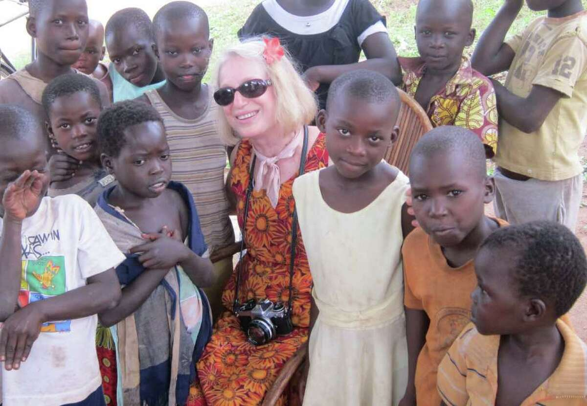 PHOTO PROVIDED BY WENDY LEVINE FINANCIAL TRAINING: Photographer Wendy Levine, surrounded by children in translator Betty Akullu's village outside Lira, traveled to Uganda with a nonprofit organization that offers financial training to villagers so that they can help themselves.
