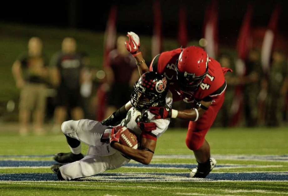 Port Arthur's Brandon Leday is tackled by North Shore's Davonte Milton after Leday caught a short pass in the first quarter as North Shore High School played Port Arthur Memorial High School at Galena Park ISD District Athletic Complex Friday, Oct. 7, 2011, in Houston. Photo: Johnny Hanson, Houston Chronicle / © 2011 Houston Chronicle