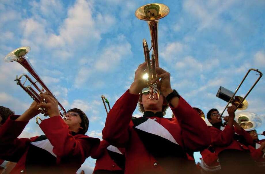 Cole Bendy (left) and Jordan Smith (center) play the trumpet as they and the Memorial High School band warm up before a football game against Cinco Ranch High School at Rhodes Stadium Friday, Oct. 7, 2011, in Katy.  (Cody Duty / Houston Chronicle Photo: Cody Duty, Houston Chronicle / © 2011 Houston Chronicle