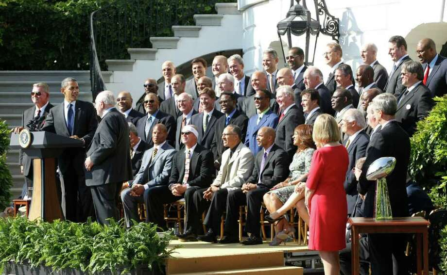 President Barack Obama stands at the podium with head coach Mike Ditka, left, and defensive coordinator Buddy Ryan, third left, as he honors the 1985 Super Bowl XX Champions Chicago Bears football team during a ceremony on the South Lawn of  the White House in Washington, Friday, Oct. 7, 2011. (AP Photo/Charles Dharapak) Photo: Charles Dharapak / AP