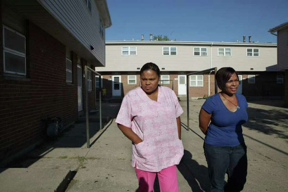 NANCY STONE : CHICAGO TRIBUNE FORMER HOME: Reynolds Wintersmith's sister Rashonda, left, and supporter Tabitha Robinson tour Rockford, Ill., housing projects where the siblings once lived. Wintersmith's mother died of a heroin overdose and his grandmother dealt drugs. Photo: Nancy Stone / Chicago Tribune