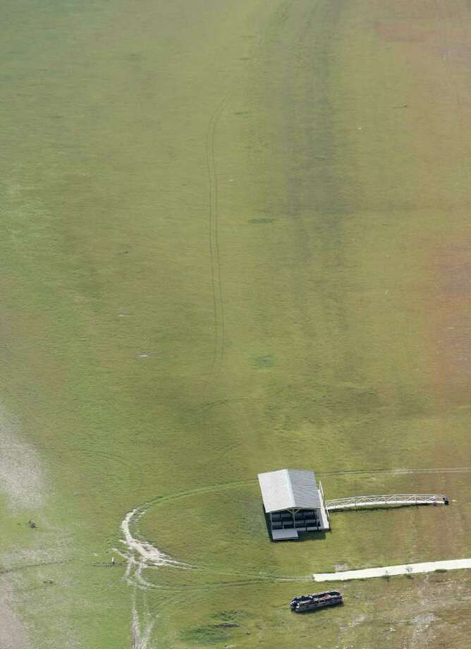 A pontoon boat and a boat dock rest, as seen in this Friday morning Oct. 7, 2011 aerial image, on the bed of what is normally Medina Lake. Everything in the image would be under water at normal pool elevation. The Texas Water Development Board reported on its website Friday that Medina Lake was 27.6 percent full. At this elevation the lake's surface area is only 35 percent of its surface area at normal pool and the lake is 44 feet low. Photo: WILLIAM LUTHER, SAN ANTONIO EXPRESS-NEWS / 2011 SAN ANTONIO EXPRESS-NEWS
