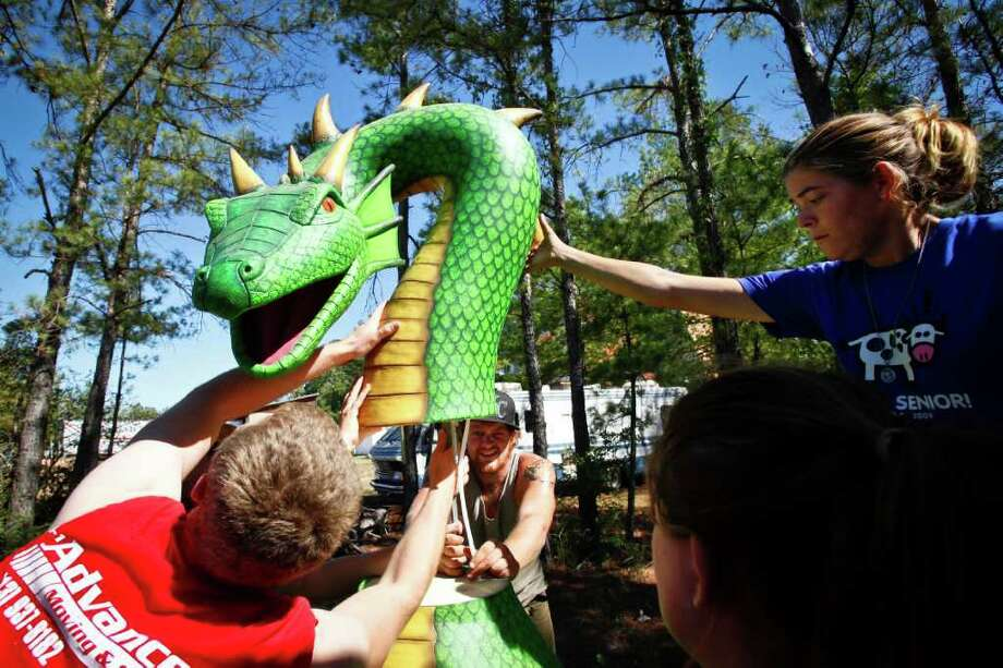 Jake Cross, center, works with Michael French, left, and Lori Asher to mount a dragon's head to its body before attaching it to the top of a ride at the Texas Renaissance Festival. The annual medieval celebration opens Saturday in Plantersville. Photo: Michael Paulsen / © 2011 Houston Chronicle