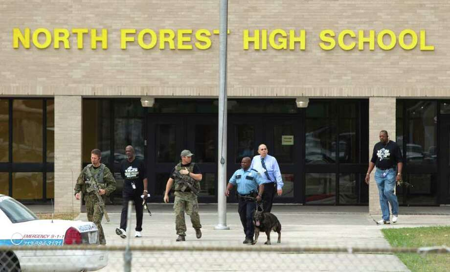 Police officials patrol outside North Forest High School during a lockdown where there were reports of a student with a gun on Friday in Houston. Photo: Brett Coomer / © 2011 Houston Chronicle