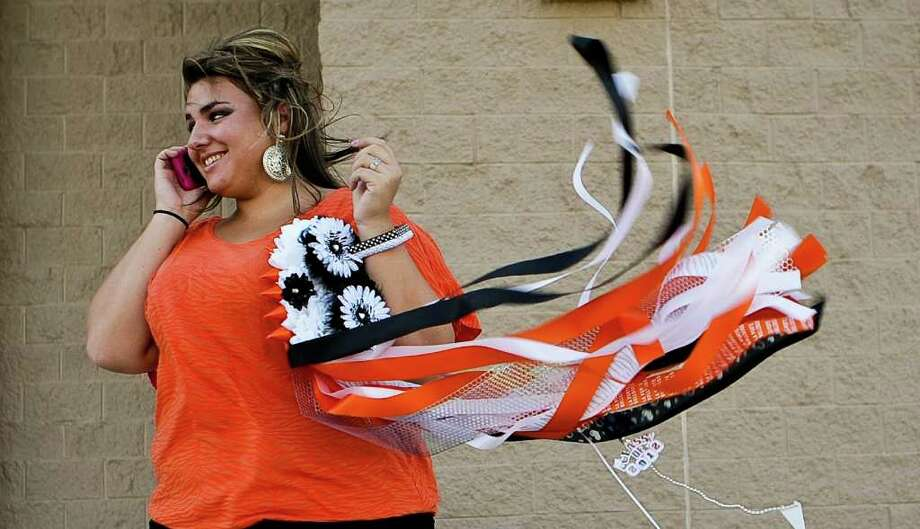 La Port High School student Sammi Lannie's mum flies in the wind as she talks on the phone before La Porte's homecomming game against Channelview at Bulldog Stadium on Friday, Oct. 7, 2011, in La Porte. Photo: Nick De La Torre, Houston Chronicle / © 2011  Houston Chronicle