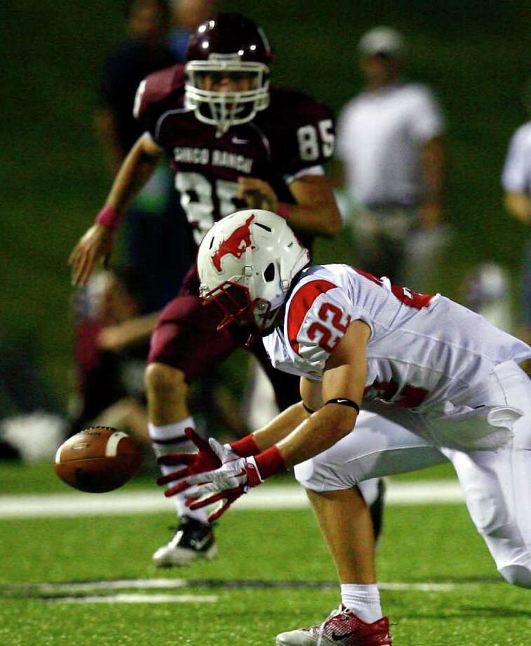 Memorial High School running back Brett Strake (22) recovers the ball on a kick-off return as Cinco Ranch High School's Jack Canfield (85) defends during the second half of a football game at Rhodes Stadium Friday, Oct. 7, 2011, in Katy. Photo: Cody Duty, Houston Chronicle / © 2011 Houston Chronicle