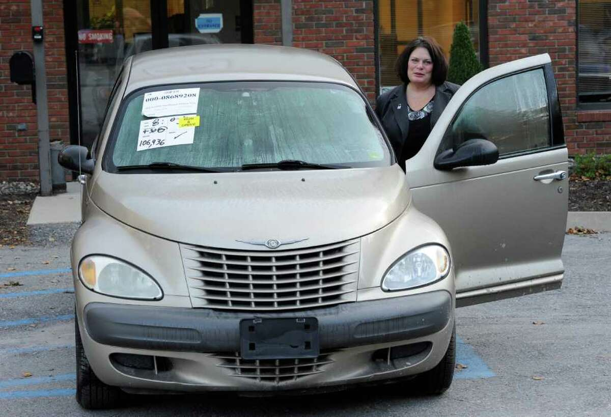Carol Lafleur, Executive Director of the Northeast Kidney Foundation stands with the donated car for local kidney foundation October 7, 2011. The car is presently housed at Insurance Auto Auctions in Schenectady, N.Y. (Skip Dickstein/Times Union)