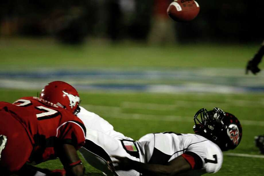 Port Arthur Memorial's Terrence Singleton (7) fumbles the ball after being hit by  Jarius Moore, left, in the second quarter as North Shore High School played Port Arthur Memorial High School at Galena Park ISD District Athletic Complex Friday, Oct. 7, 2011, in Houston. Photo: Johnny Hanson, Houston Chronicle / © 2011 Houston Chronicle