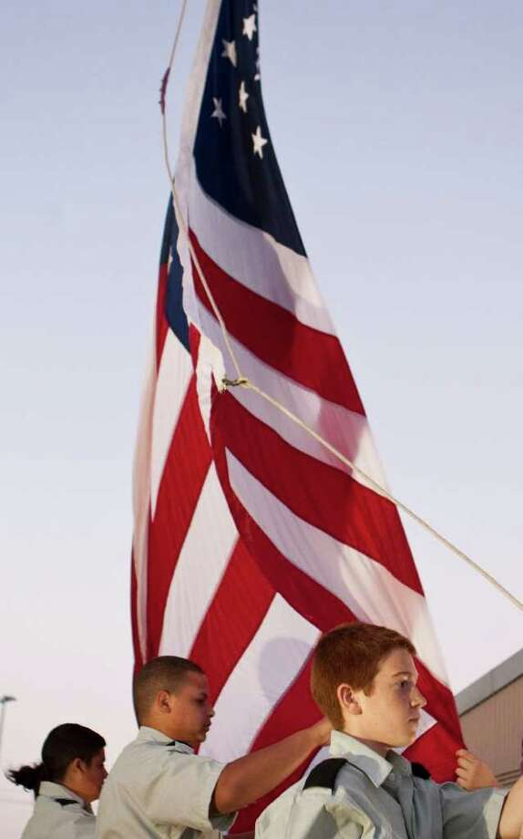 Austin Hagemeister, of La Porte High School's Army JROTC, performs his duty as the halyard holder as the U.S. flag is raised during he playing of the National Anthem before a District 21-5A football game between La Porte High School and Channelview High SChool at Bulldog Stadium on Friday, Oct. 7, 2011, in La Porte. Photo: Nick De La Torre, Houston Chronicle / © 2011  Houston Chronicle