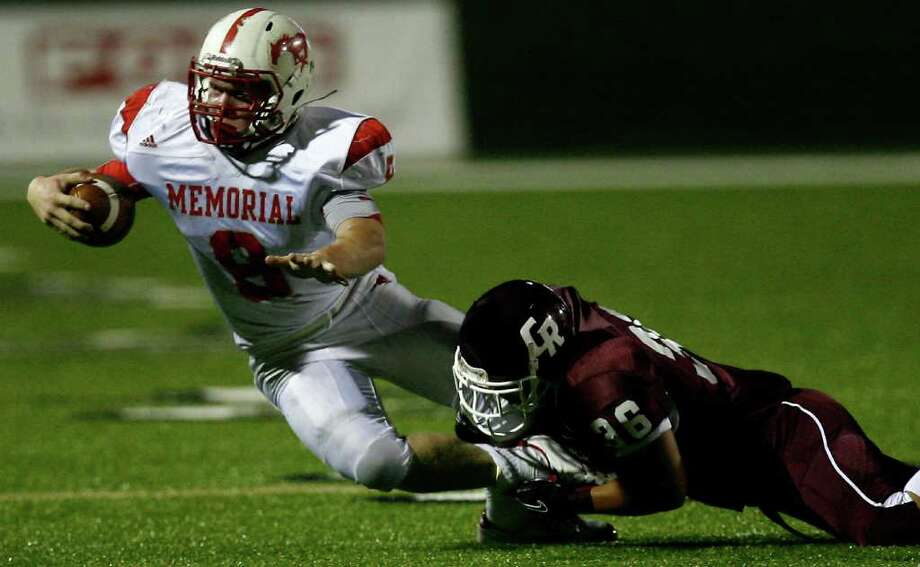 Memorial High School running back Boomer White (left) is brought down by the Cinco Ranch High School defensive back Kevin Yates during the second half of a football game at Rhodes Stadium Friday, Oct. 7, 2011, in Katy. Photo: Cody Duty, Houston Chronicle / © 2011 Houston Chronicle