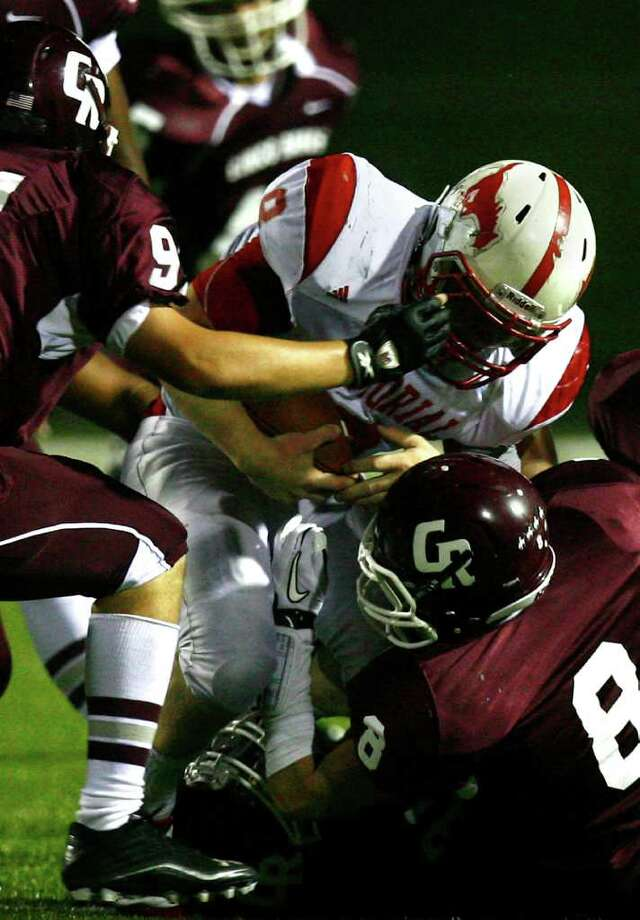 Memorial High School running back Boomer White (8) is brought down by the Cinco Ranch High School's Nick Knoth (94) and Remington Hajdik (8) during the second half of a football game at Rhodes Stadium Friday, Oct. 7, 2011, in Katy. Photo: Cody Duty, Houston Chronicle / © 2011 Houston Chronicle