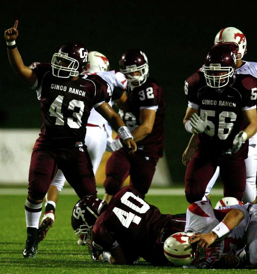Cinco Ranch High School's Anand Chaudhari (43) and Connor Siegmund (56) react after Bohao Cheng (not pictured) and Josh Firth (40) recovered a fumble against Memorial High School during the second half of a football game at Rhodes Stadium Friday, Oct. 7, 2011, in Katy. Photo: Cody Duty, Houston Chronicle / © 2011 Houston Chronicle