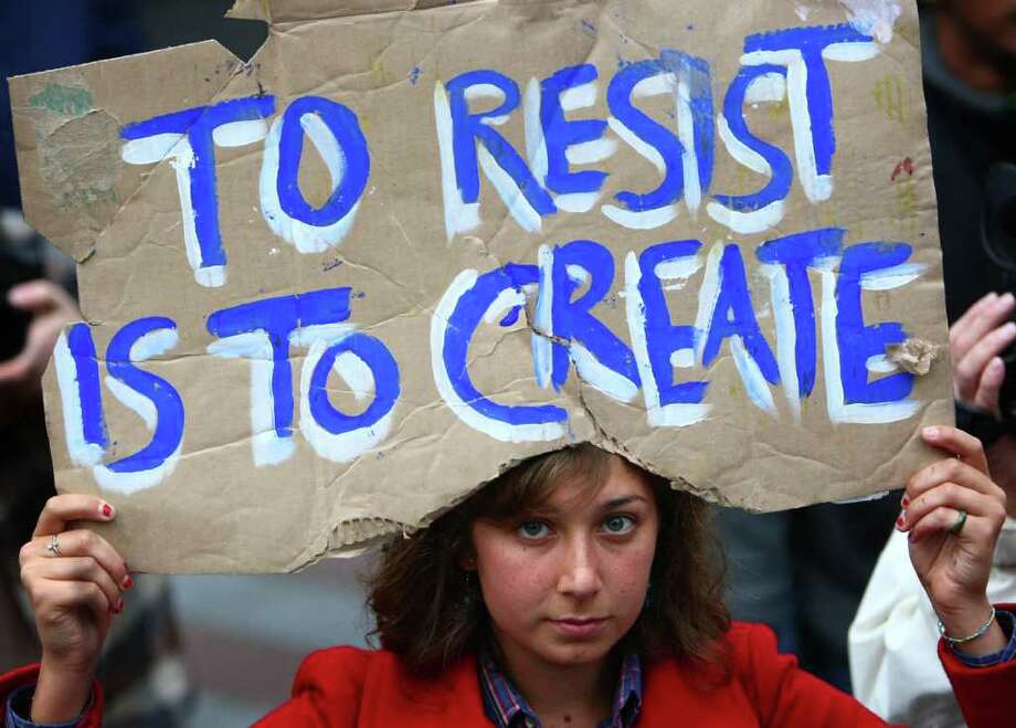 Laura Robison of Seattle holds up a sign during a combined Occupy Seattle and Act Now to Stop War and End Racism (ANSWER) protest at Westlake Park on Friday, October 7, 2011. Hundreds of people gathered for the two coinciding protests. Friday marked the 10 year anniversary of the beginning of U.S. war in Afghanistan. Photo: JOSHUA TRUJILLO / SEATTLEPI.COM