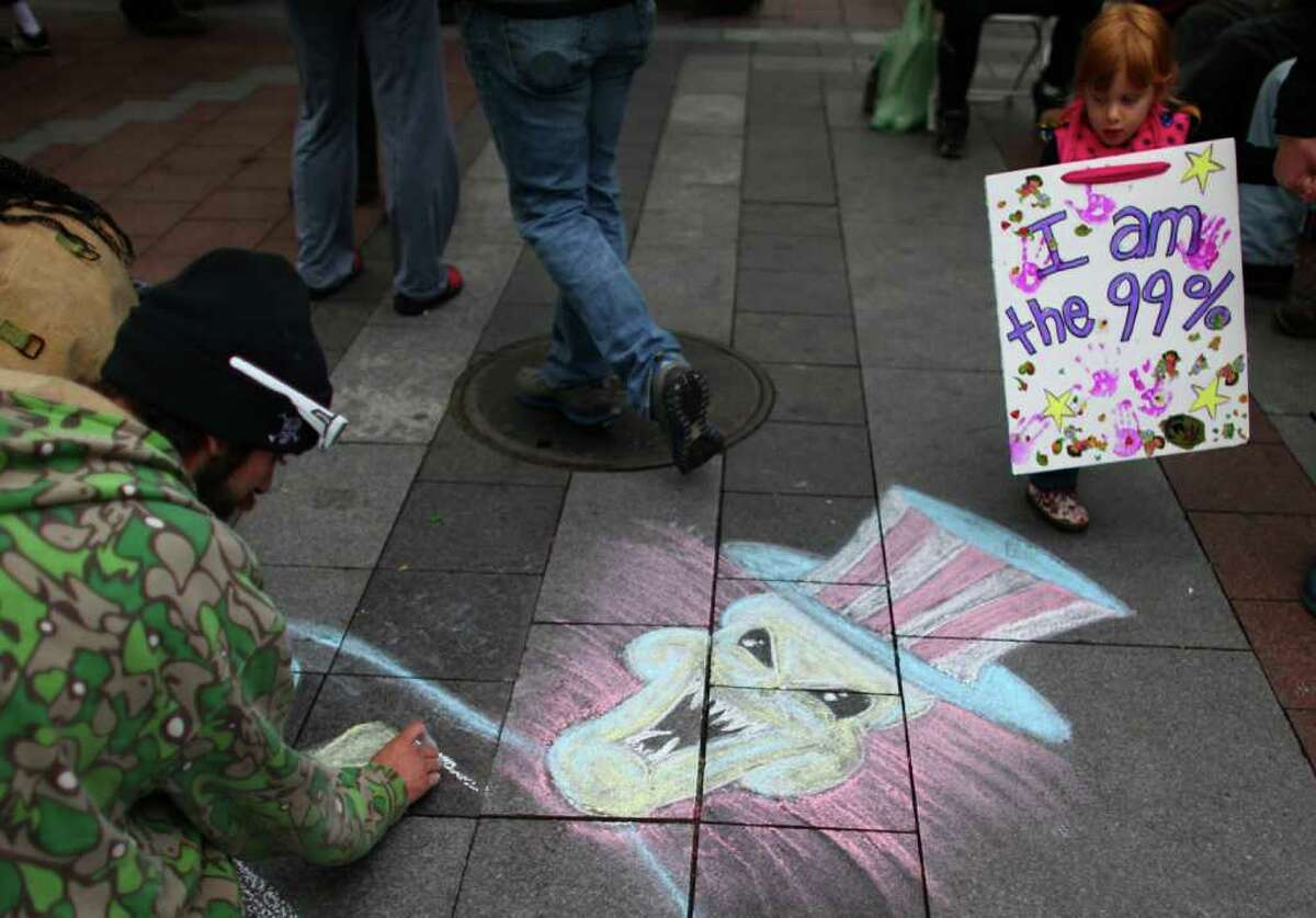 Mercedes Huddleston, 3, walks past chalk art during a combined Occupy Seattle and Act Now to Stop War and End Racism (ANSWER) protest at Westlake Park on Friday, October 7, 2011. Hundreds of people gathered for the two coinciding protests. The Occupy Seattle demonstration is an offshoot of the Occupy Wall Street protest in New York City.