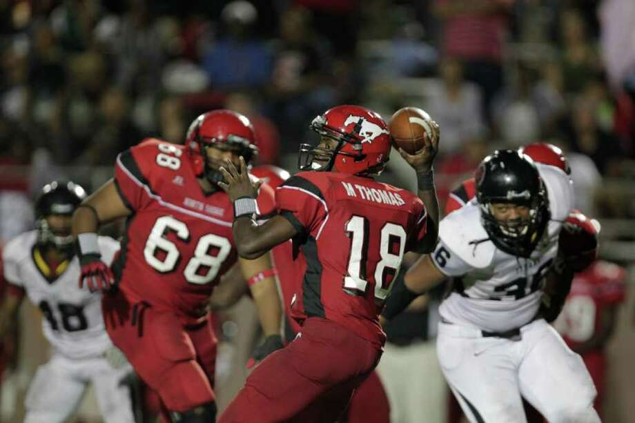 Port Arthur Memorial's Donavan Banks, left, looks to sack North Shore's quarterback Micha Thomas (18) as Memorial defeated North Shore High School 14-7 at Galena Park ISD District Athletic Complex Friday, Oct. 7, 2011, in Houston. Photo: Johnny Hanson, Houston Chronicle / © 2011 Houston Chronicle