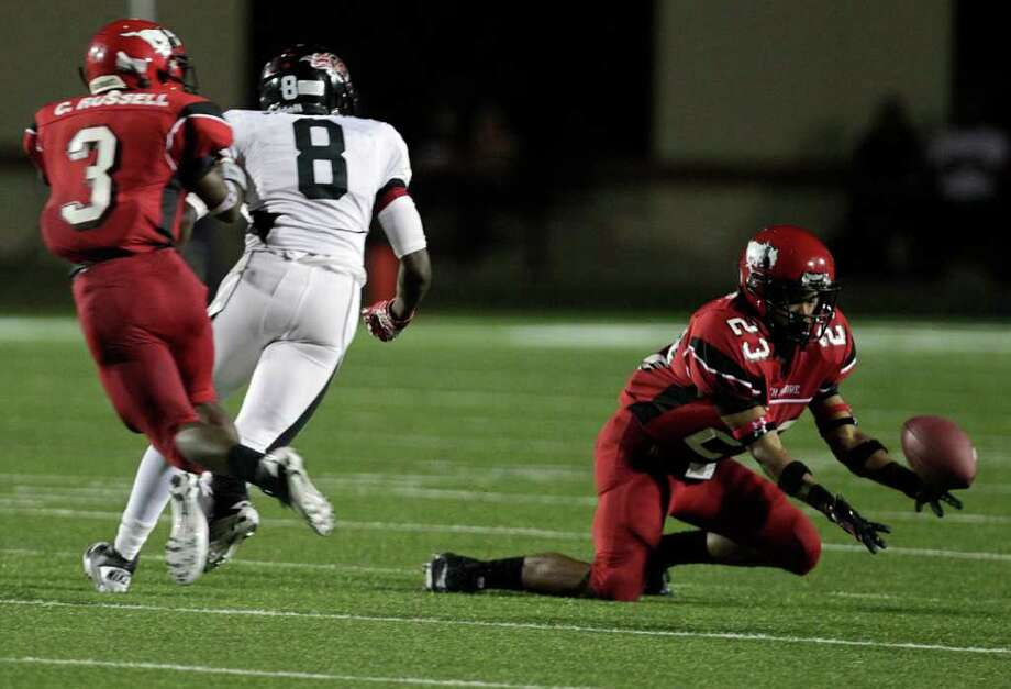 North Shore's Jacoby Walker (23) misses an interception in the third quarter next to Port Arthur Memorial's John Leday (8) and North Shore's Nathan Holmes (3) Port Arthur Memorial High School defeated North Shore High School 14-7 at Galena Park ISD District Athletic Complex Friday, Oct. 7, 2011, in Houston. Photo: Johnny Hanson, Houston Chronicle / © 2011 Houston Chronicle