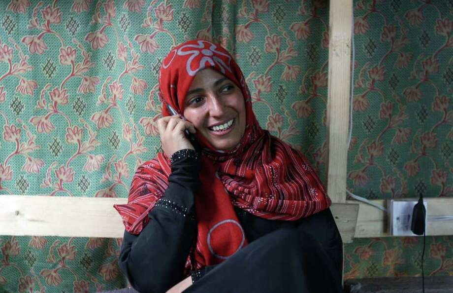 """Yemeni journalist and activist Tawakkul Karman speaks on the phone from a protest tent in Sanaa on October 7, 2011 following the announcement that she was one of three women awarded the Nobel Peace Prize. Karman, who won the award along with Liberian President Ellen Johnson Sirleaf and Liberian """"peace warrior"""" Leymah Gbowee, became the first Arab woman to win the Nobel Peace Prize and she dedicated it to """"all the activists of the Arab Spring"""". AFP PHOTO/ MOHAMMED HUWAIS (Photo credit should read MOHAMMED HUWAIS/AFP/Getty Images) Photo: MOHAMMED HUWAIS"""