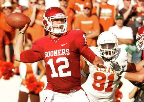 Oklahoma quaterback Landry Jones (12) throws as Texas defensive end Jarrett Brown (81) rushes during the second half of their NCAA football game at the Cotton Bowl in Dallas, on Saturday, Oct. 2, 2010. Oklahoma won 28-20. Photo: AP
