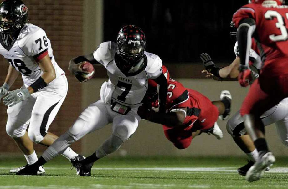 JOHNNY HANSON: CHRONICLE HEAVY LOAD: Port Arthur Memorial's Terrence Singleton, left, carries both the football and North Shore defender Justin Provost on a first-quarter run Friday night. Photo: Johnny Hanson / © 2011 Houston Chronicle