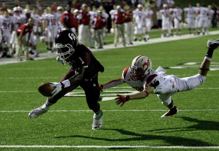 CODY DUTY: CHRONICLE ALMOST THERE: Cinco Ranch receiver James Rhoden, left, lunges toward the end zone to score on a 15-yard pass in the first quarter, escaping the grasp of Memorial's Will Bigelow. Photo: Cody Duty / © 2011 Houston Chronicle