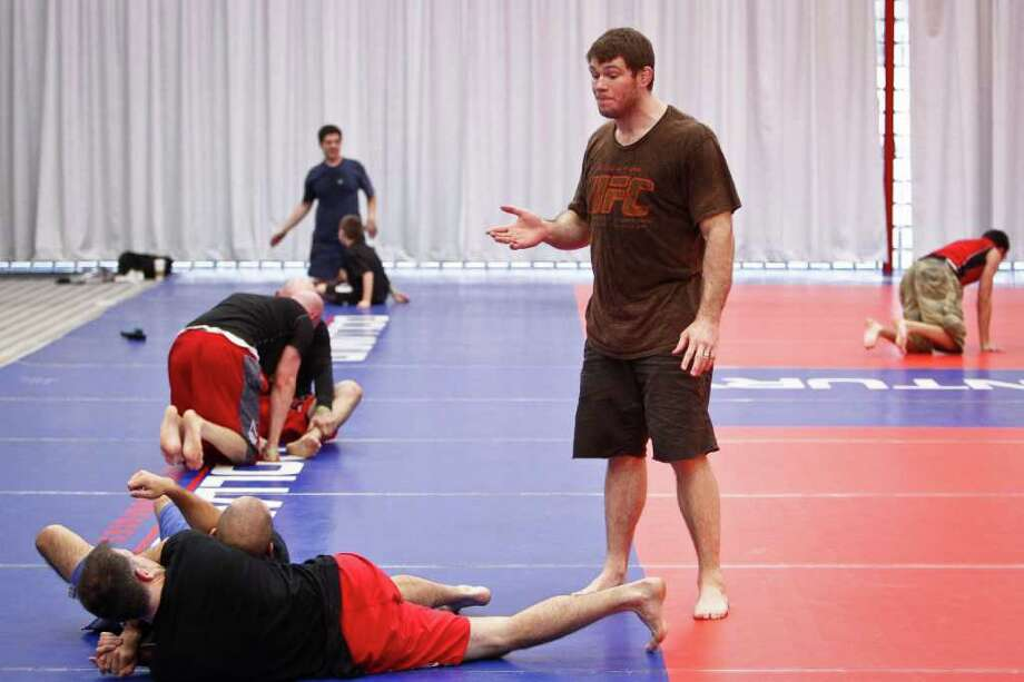 UFC fighter Forrest Griffin (right) gives instructions to Matt Vardeman (left) and Michael Shields (second from left) during a Training and Development Session at the UFC Fan Expo at the George R. Brown Convention Center, Friday, Oct. 7, 2011, in Houston. Photo: Michael Paulsen, Houston Chronicle / © 2011 Houston Chronicle