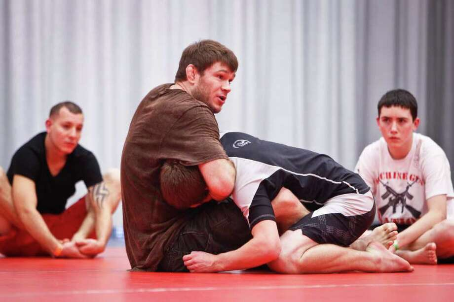 UFC fighter Forrest Griffin (center) gives instructions to students as he wrestles Josh Altum, 14, during a Training and Development Session at the UFC Fan Expo at the George R. Brown Convention Center, Friday, Oct. 7, 2011, in Houston. Photo: Michael Paulsen, Houston Chronicle / © 2011 Houston Chronicle
