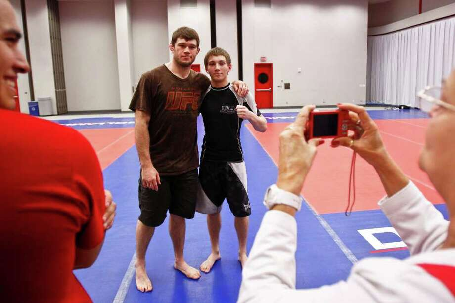 UFC fighter Forrest Griffin (second from left) poses for a photo with Josh Altum, 14, during a Training and Development Session at the UFC Fan Expo at the George R. Brown Convention Center, Friday, Oct. 7, 2011, in Houston. Photo: Michael Paulsen, Houston Chronicle / © 2011 Houston Chronicle