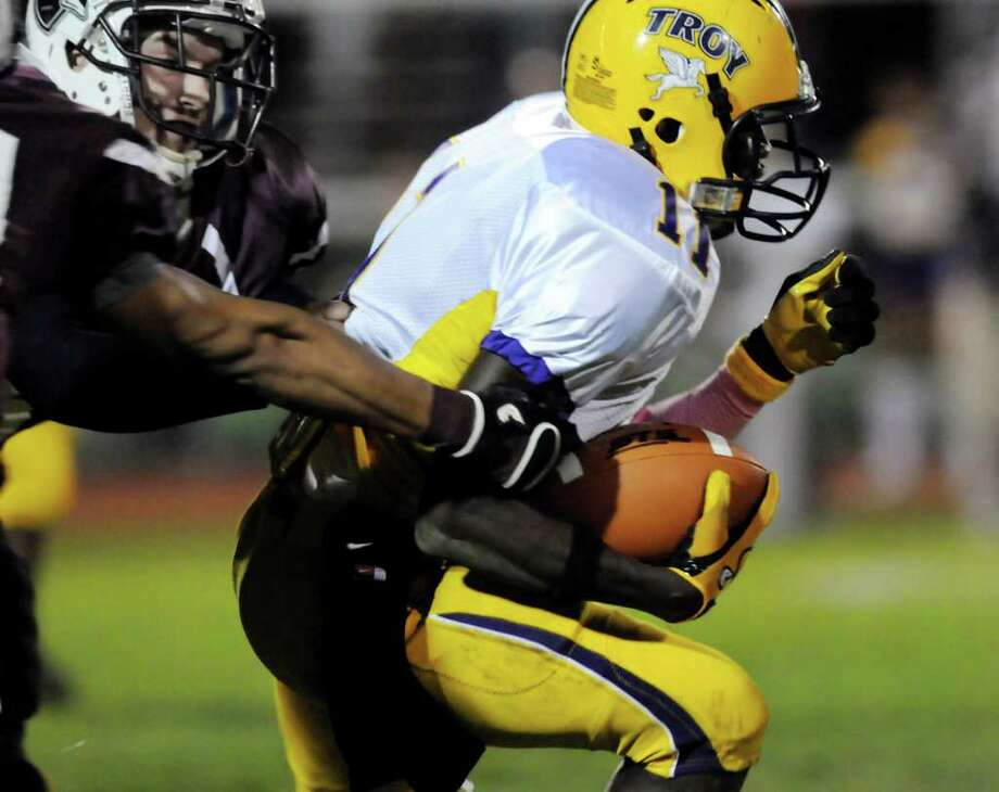 Troy's Karmin Cooney (11), right, fights off Lansingburgh defenders during their football game on Friday, Oct. 7, 2011, at Lansingburgh High in Lansingburgh, N.Y. (Cindy Schultz / Times Union) Photo: Cindy Schultz