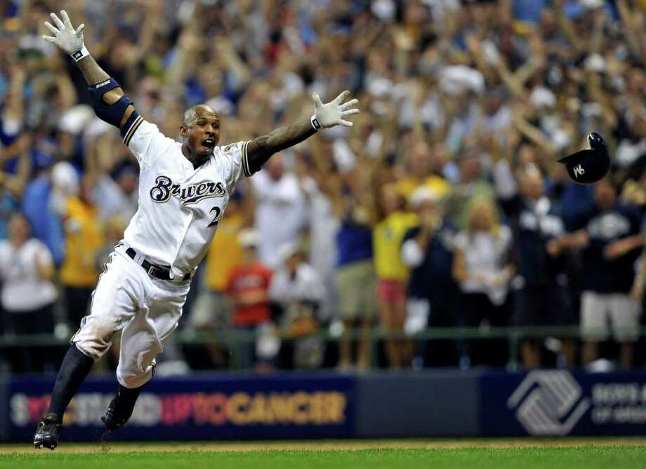 Milwaukee Brewers' Nyjer Morgan (2) celebrates after hitting the game-winning single in the 10th inning of Game 5 of baseball's National League division series against the Arizona Diamondbacks Friday, Oct. 7, 2011, in Milwaukee. The Brewers won 3-2 to advance to the National League championship series. (AP Photo/Jim Prisching) Photo: Jim Prisching