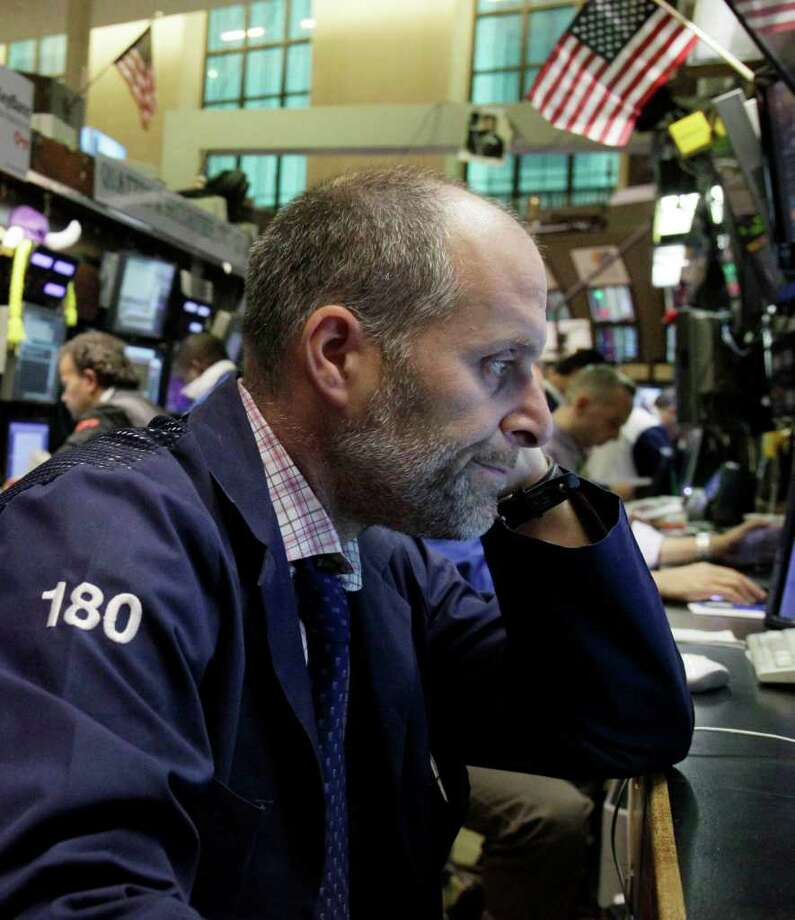 In this Oct. 4, 2011 photo, trader Jason Weisberg works on the floor of the New York Stock Exchang. Investors were cautious on Friday, Oct. 7, 2011, ahead of U.S. jobs figures, with stocks down slightly after enjoying a couple of bumper days on hopes of a Europe-wide plan to fix the banking sector.(AP Photo/Richard Drew) Photo: Richard Drew