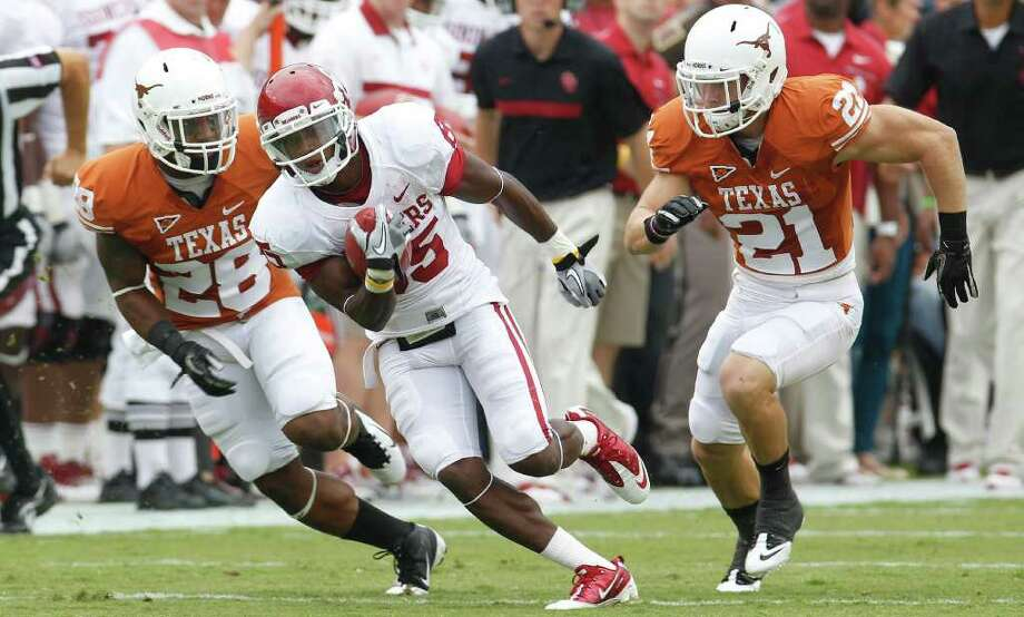 Oklahoma wide receiver Ryan Broyles (85) runs past Texas cornerback Quandre Diggs (28) and safety Blake Gideon (21) after catching a pass during the first quarter of an NCAA college football game at the Cotton Bowl in Dallas, Saturday, Oct. 8, 2011.  (AP Photo/LM Otero) Photo: LM Otero, Associated Press / AP