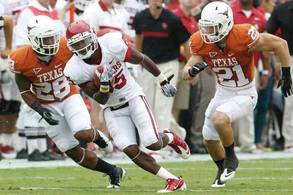 Oklahoma wide receiver Ryan Broyles (85) runs past Texas cornerback Quandre Diggs (28) and safety Blake Gideon (21) after catching a pass during the first quarter of an NCAA college football game at the Cotton Bowl in Dallas, Saturday, Oct. 8, 2011.  (AP Photo/LM Otero)
