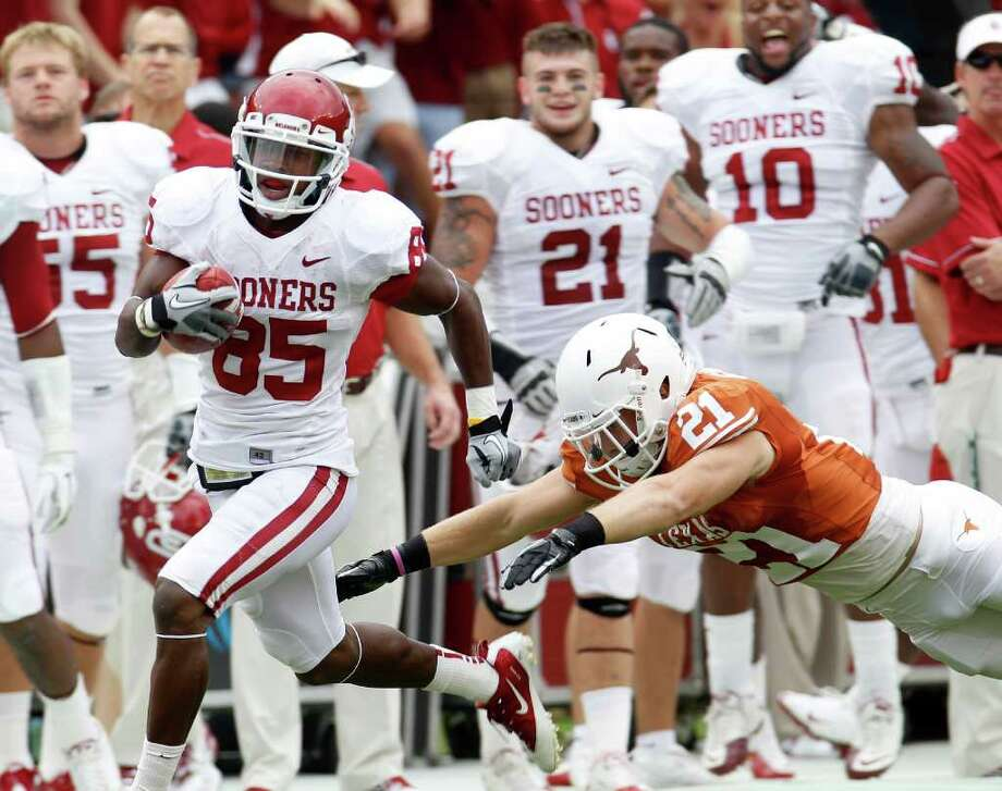 Oklahoma wide receiver Ryan Broyles (85) evades Texas safety Blake Gideon (21) after his reception in the first quarter of ab NCAA college football game at the Cotton Bowl in Dallas, Saturday, Oct. 8, 2011.  (AP Photo/LM Otero) Photo: LM Otero, Associated Press / AP