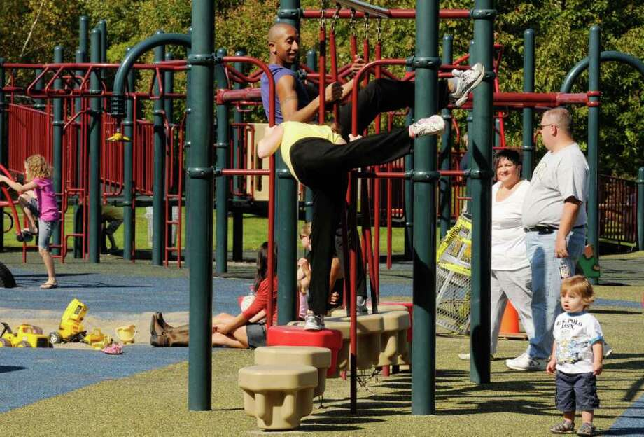 Dancers Andre' Robles and Laura Teeter of the Ellen Sinopoli Dance Company perform a dance piece incorporating the playground at The Crossings in Colonie, NY Saturday Oct. 8, 2011.( Michael P. Farrell/Times Union) Photo: Michael P. Farrell
