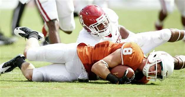 Texas wide receiver Jaxon Shipley (8) is knocked to the turf by Oklahoma defensive end Ronnell Lewis (56) during the second half of an NCAA college football game at the Cotton Bowl in Dallas, Saturday, Oct. 8, 2011. (AP Photo/Mike Fuentes)