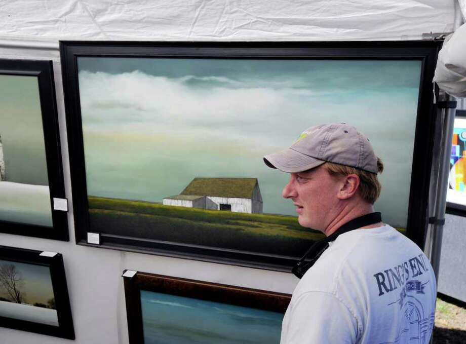 Brian McIntosh of Rye, N.Y., gets a look at the central Ohio landscapes of painter, Gary Stretar, during the 30th annual Outdoor Arts Festival at the Bruce Museum in Greenwich, Saturday morning, Oct. 8, 2011. The festival runs Sunday from 10 a.m. to 5 p.m. on the museum grounds at 1 Museum Drive. Photo: Bob Luckey / Greenwich Time