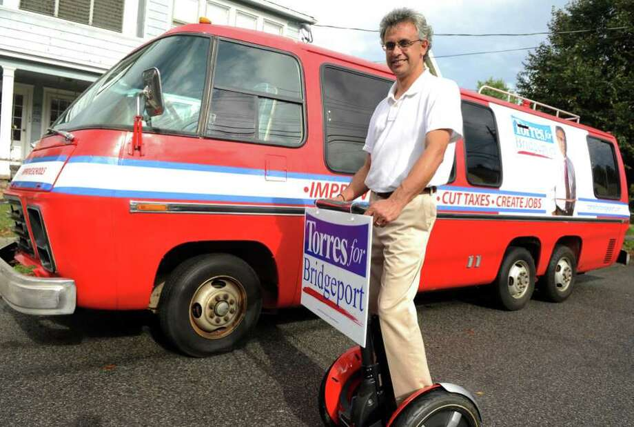 Bridgeport mayoral candidate, Republican Rick Torres, on his Segway, poses in front of a 1975 red van that will serve as his primary transportation throughout the campaign season.  Torres hopes to gain more exposure with his unconventional approach to campaigning. Photo: Autumn Driscoll