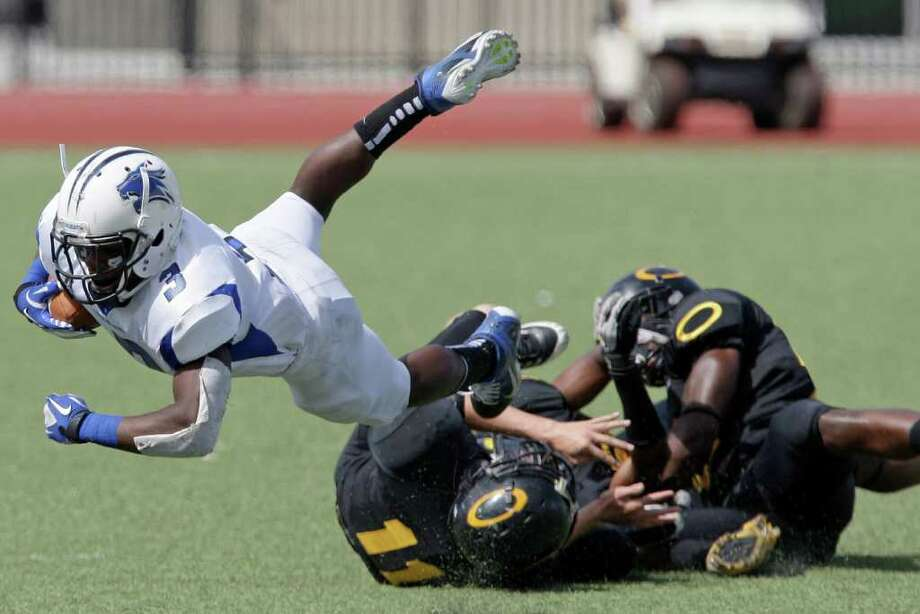 10/8/11: Running back Torence Porter #3 of the Dekaney Wildcats is tripped up by  defensive back Austin Ondrej #11of the Klein Oak Panthers  in a high school football game at Klein Memorial Stadium in Klein, Texas. For the Chronicle: Thomas B. Shea Photo: For The Chronicle: Thomas B. She