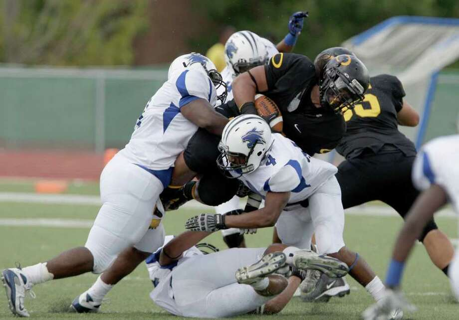 10/8/11: Running back E.J. Fatu #44  of the Klein Oak Panthers is ganged tackled by the Dekaney Wildcats defense  in a high school football game at Klein Memorial Stadium in Klein, Texas. For the Chronicle: Thomas B. Shea Photo: For The Chronicle: Thomas B. She