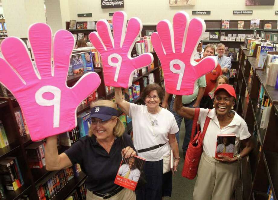 "JOE BURBANK : ORLANDO SENTINEL REVOLUTION NO. 9: Supporters of 2012 Republican presidential contender Herman Cain hold up ""9-9-9"" hands, a reference to Cain's proposed tax overhaul, during a book signing Wednesday in The Villages, Fla. Photo: Joe Burbank / Orlando Sentinel"