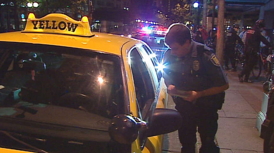 A Seattle police officer tickets a taxi driver who honked in support of the Occupy Seattle protesters Friday night.