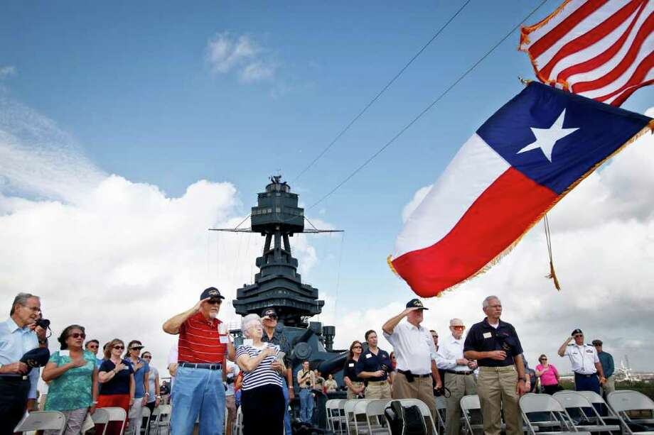 Five former crew members and their families salute the colors. Photo: Michael Paulsen / © 2011 Houston Chronicle