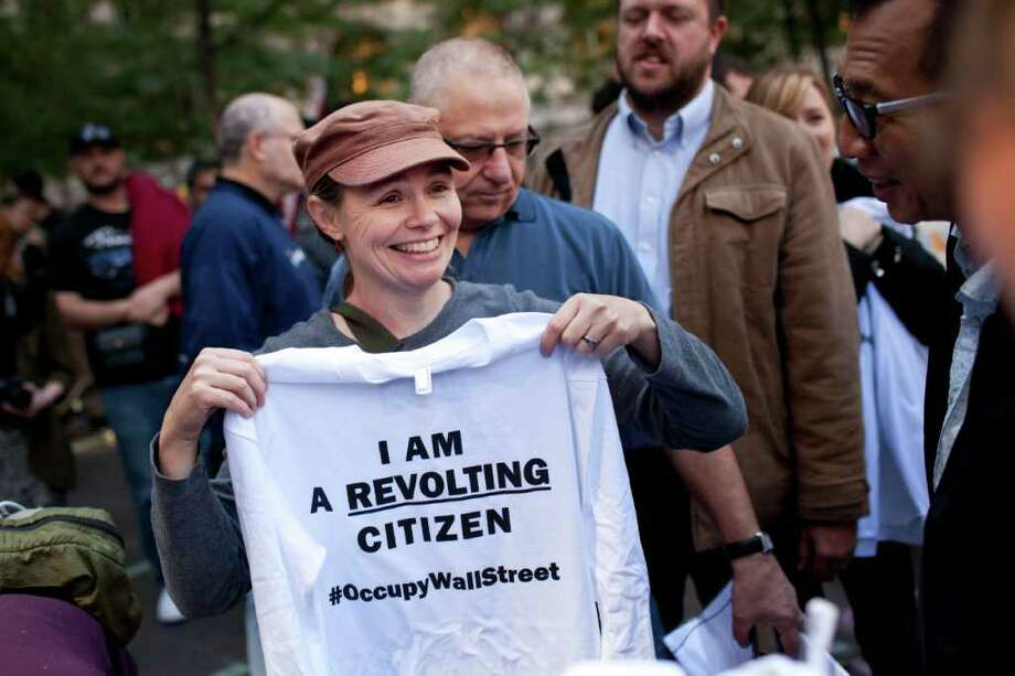 "Cate Nolan, from Brooklyn, New York, holds up a shirt that says ""I Am A Revolting Citizen"" while participating in the ""Occupy Wall Street"" protests in Zuccotti Park, in New York, on Friday, Oct. 7, 2011. Nolan and her husband, Jim Leonard had 100 of the shirts made to hand out to people, for free, at the protest. (AP Photo/Andrew Burton) Photo: Andrew Burton / FRE170478 AP"