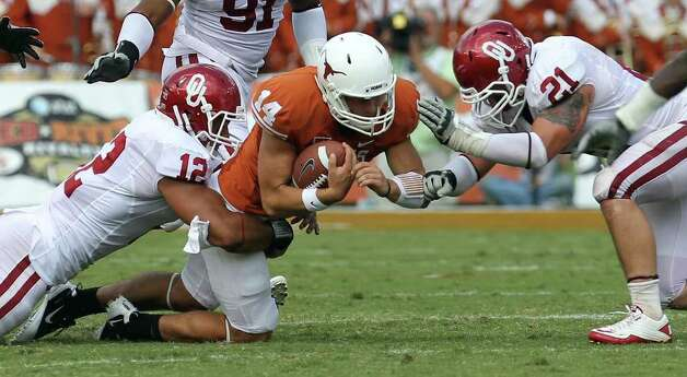 Oklahoma's Travis Lewis (12) and Tom Wort (21) tackle Texas quarterback David Ash (14) in the second half of the Red River Rivalry at the Cotton Bowl in Dallas on Saturday, Oct. 8, 2011. The Sooners defeated the Longhorns, 55-17. Kin Man Hui/kmhui@express-news.net Photo: Kin Man Hui, Kin Man Hui / Kmhui@express-news.net / San Antonio Express-News