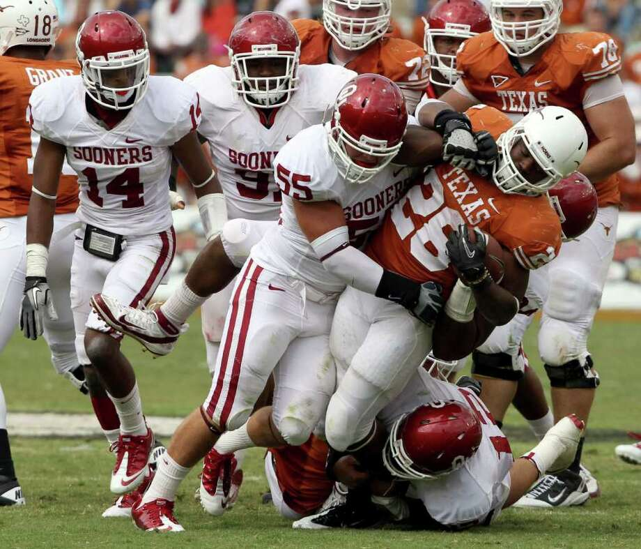 Richard W. Rodriguez : Fort Worth Star-Telegram/MCT LOWERING THE BOOM: Oklahoma linebacker Jaydan Bird (55), gets a lot of help from his friends as he brings Texas running back Malcolm Brown (28) to a grinding halt during the Sooners 55-17 annihilation of the Longhorns on Saturday. Photo: Richard W. Rodriguez / Fort Worth Star-Telegram