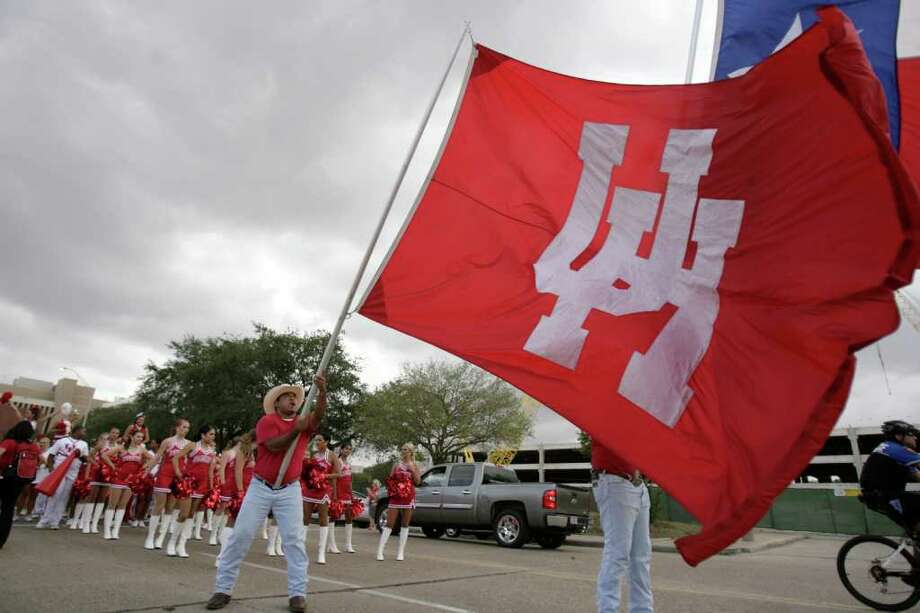 Gabe Salazar, a Frontiersman and UH student tries to hold up the UH flag as wind gusts past him before a NCAA football game at Robertson Stadium on Saturday, Oct. 8, 2011, in Houston. Photo: Nick De La Torre, Houston Chronicle / © 2011  Houston Chronicle