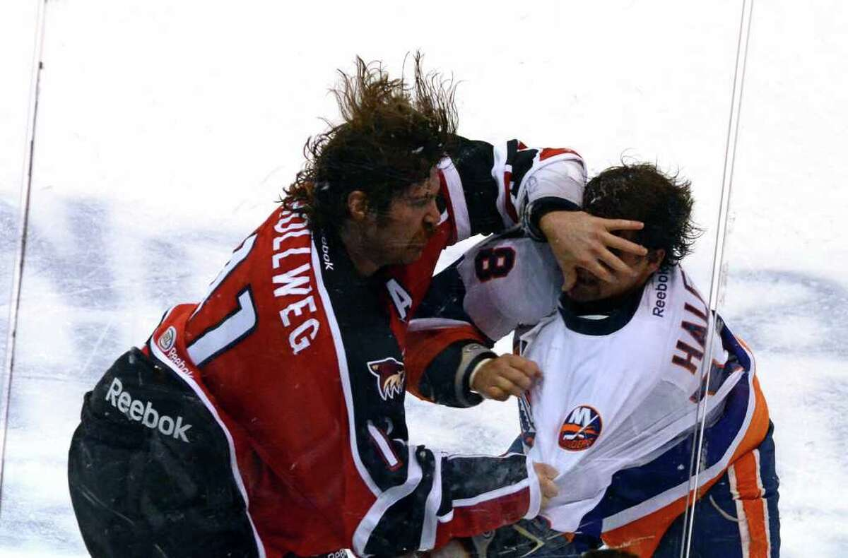 Portland Pirates' Ryan Hollweg palms Bridgeport Sound Tigers' Micheal Haley's face during a brawl on the ice during the AHL season opener at the Webster Bank Arena in Bridgeport on Saturday, Oct. 8, 2011.