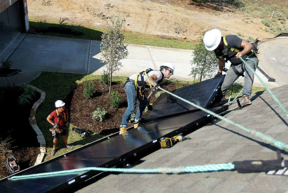 Richard Sherwood, right, co-owner of Adaptive Solar Design of Houston, and Danny Furness install a roof panel on a home in The Woodlands. The solar energy industry in Texas is undeterred by recent manufacturing failures elsewhere.