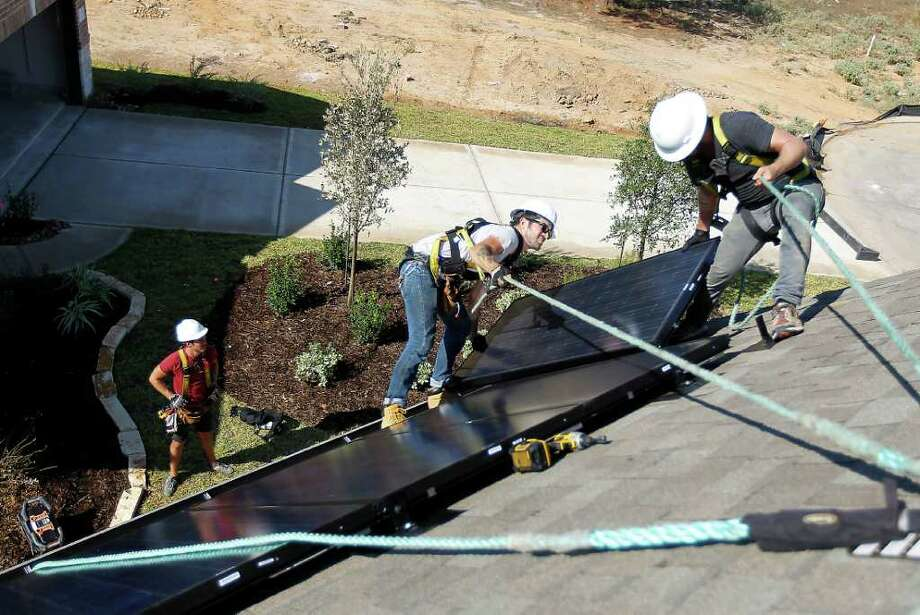 Richard Sherwood, right, co-owner of Adaptive Solar Design of Houston, and Danny Furness install a roof panel on a home in The Woodlands. The solar energy industry in Texas is undeterred by recent manufacturing failures elsewhere. Photo: Karen Warren / © 2011 Houston Chronicle
