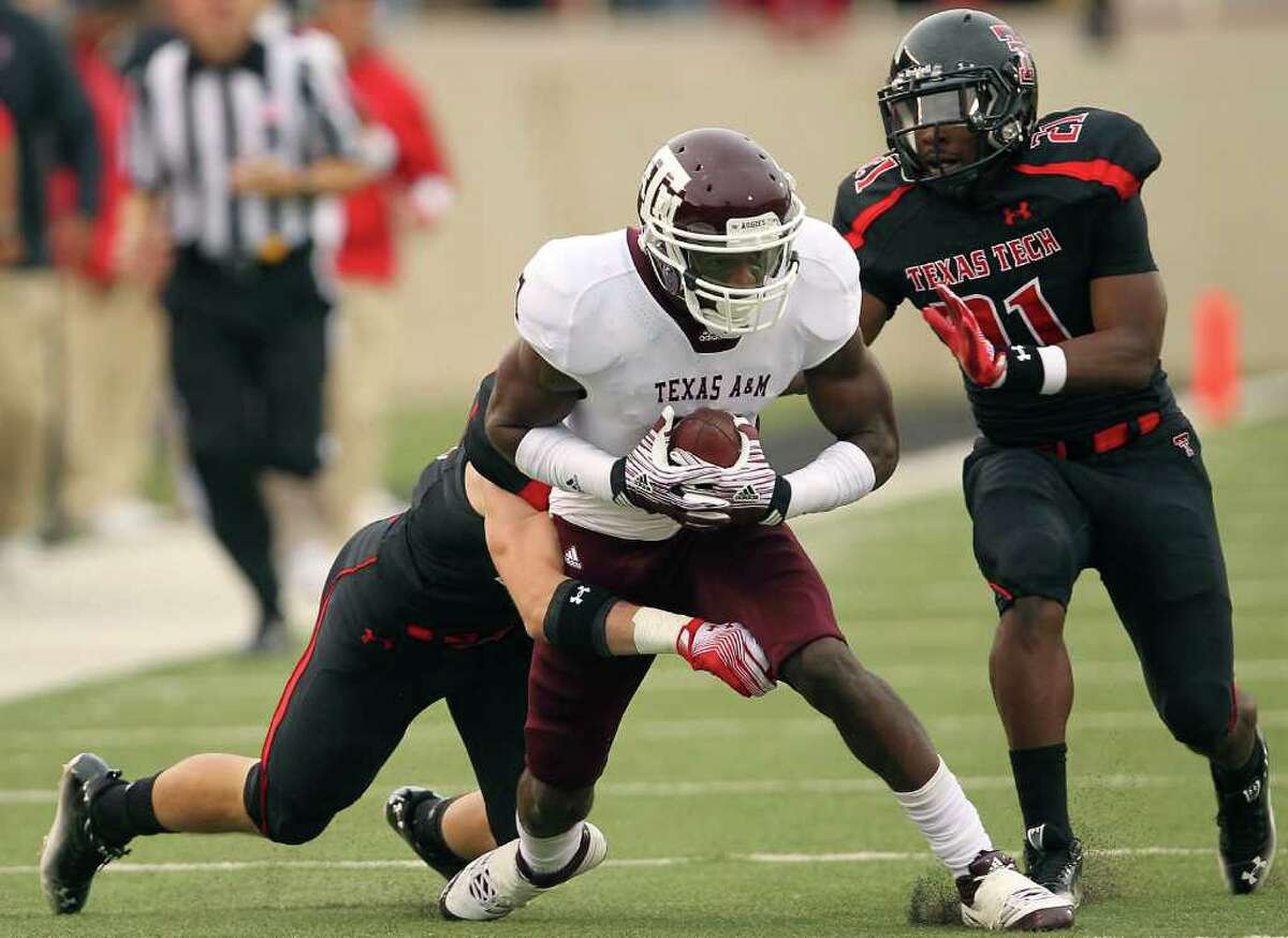 Texas A&M's Uzoma Nwachukwu, center, tries to get past Texas Tech's Cody Davis, left, and Jarvis Phillips (21) during an NCAA college football game in Lubbock, Texas on Saturday, Oct. 8, 2011. (AP Photo/The Lubbock Avalanche-Journal, Stephen Spillman)